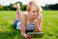 Pretty woman using her tablet and relaxing on the grass - PhotoDune Item for Sale