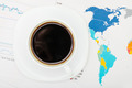 Coffee cup over world map and financial documents - view from top - PhotoDune Item for Sale