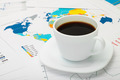Coffee cup over world map and some financial documents - PhotoDune Item for Sale