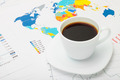 Coffee cup above world map and some financial documents - PhotoDune Item for Sale