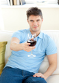 Charming young man sitting on a sofa holding wineglass