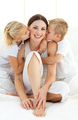 Adorable siblings kissing their mother sitting on a bed