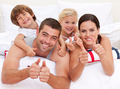 Family playing in bed with thumbs up