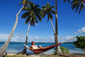 Young woman in bikini sitting in a hammock between palm trees, Ofu island, Vavau group, Tonga - PhotoDune Item for Sale
