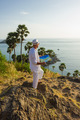 A young man in a white suit on the beach with a map - PhotoDune Item for Sale