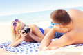 Woman taking a picture of her boyfriend at the beach - PhotoDune Item for Sale