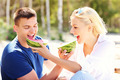 Happy couple eating watermelon at the beach - PhotoDune Item for Sale