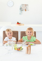 Adorable siblings eating a salad together in the kitchen