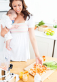 Radiant mother preparing food for her adorable baby in the kitch