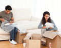 Joyful couple packing glasses together in the living room