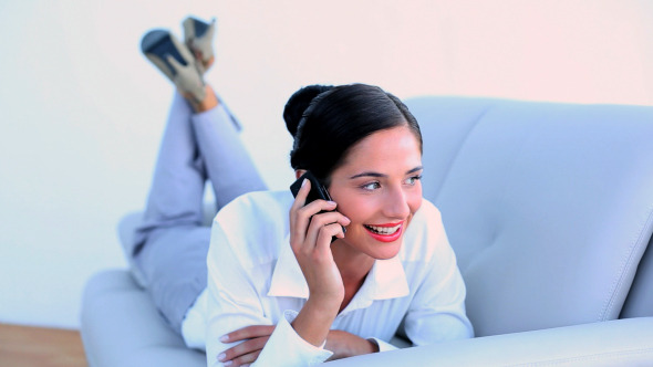 Attractive Businesswoman Lying On Couch On Phone