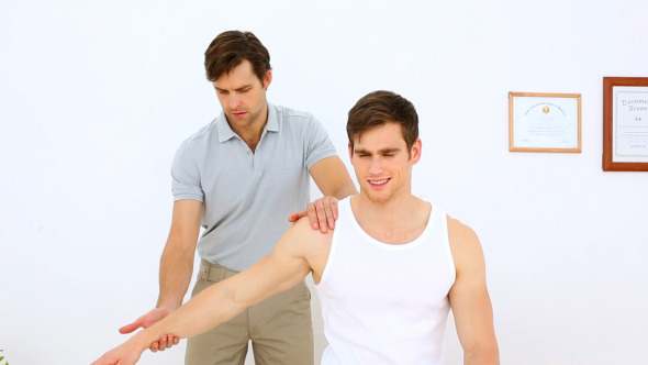 Physiotherapist Moving Patients Arm