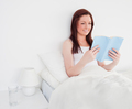 Pretty red-haired woman reading a book while sitting on her bed