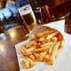 Potatoes fries in a little white paper bag on wood table in brus - PhotoDune Item for Sale