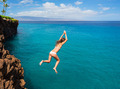 Woman jumping off cliff into the ocean - PhotoDune Item for Sale