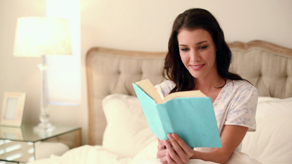 Beautiful Brunette Sitting In Bed Reading A Book
