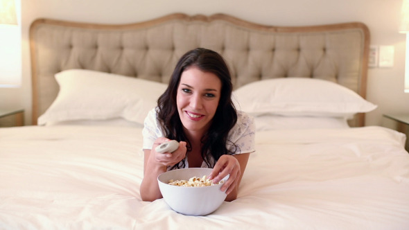 Beautiful Brunette Lying On Bed Eating Popcorn