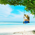 Woman in blue dress swinging at beach - PhotoDune Item for Sale