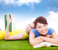 smiling pretty students lying on the grassland with books in the park - PhotoDune Item for Sale