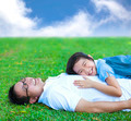 father and daughter lying on a meadow in the park with blue sky - PhotoDune Item for Sale