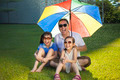 Father and two daughters sitting on a meadow with colorful umbrella in the park - PhotoDune Item for Sale