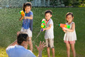 little guys using water guns to spray their father in the park - PhotoDune Item for Sale