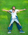 young father and son lying on a meadow together in the park - PhotoDune Item for Sale