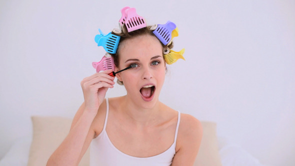 Young Model In Hair Rollers Putting On Mascara