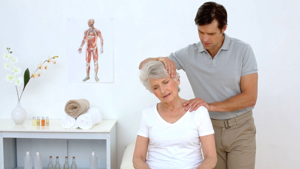 Physiotherapist Checking Senior Patients Neck