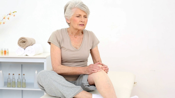 Injured Patient Rubbing Her Painful Knee