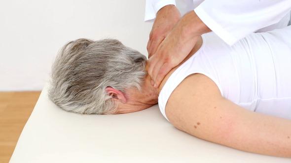 Doctor Massaging Senior Patients Shoulders