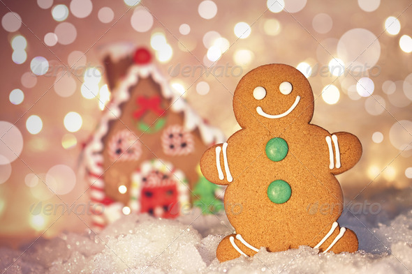 Gingerbread man cookie standing beside house - Stock Photo - Images