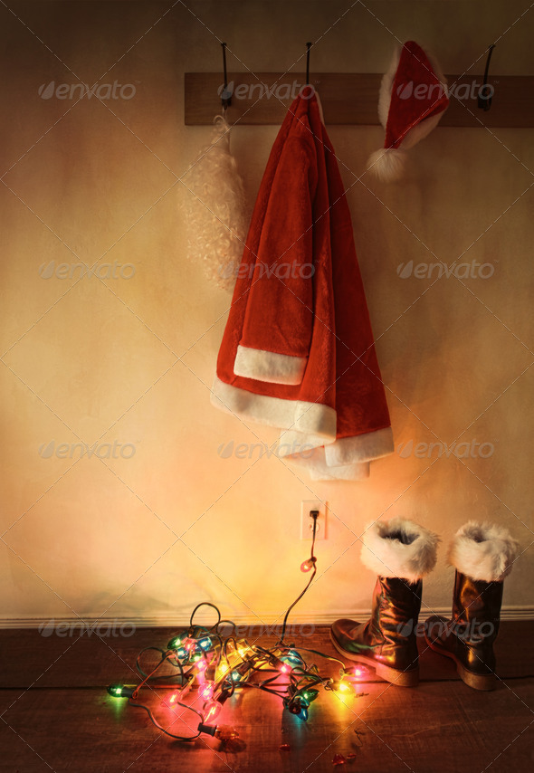 Santa costume hanging on coat hook with Christmas lights - Stock Photo - Images