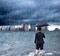 business man holding an umbrella and standing  with cloudburst background  - PhotoDune Item for Sale