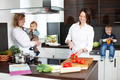Woman Preparing Food With Friend And Children In Kitchen - PhotoDune Item for Sale