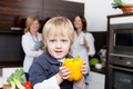 Boy Holding Yellow Capsicum With Women In Background - PhotoDune Item for Sale