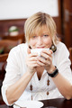 Woman Holding Coffee Cup At Table In Restaurant - PhotoDune Item for Sale