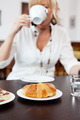 Croissant On Table With Woman Drinking Coffee In Background - PhotoDune Item for Sale