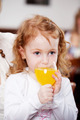 Girl Drinking Orange Juice While Looking Away In Restaurant - PhotoDune Item for Sale