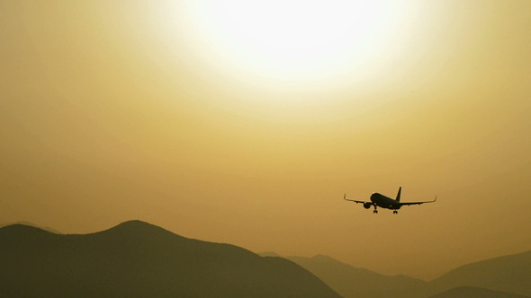 Airplane Flying at Low Altitude at Sunset