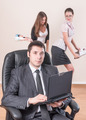 Business man works with laptop over female colleagues background - PhotoDune Item for Sale