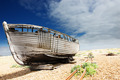 wooden fishing boat left to rot and decay on the shingle beach at Dungeness, England, UK. - PhotoDune Item for Sale