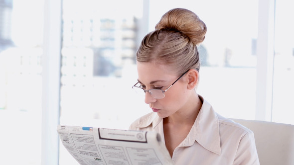 Content Blonde Businesswoman Reading Newspaper