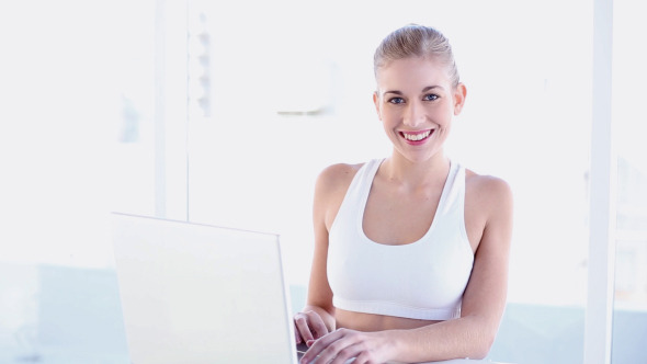 Sporty Smiling Blonde Using Laptop