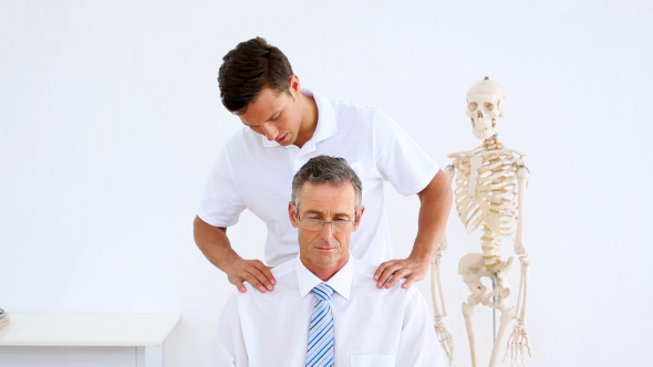 Physiotherapist Giving Businessman A Shoulder Rub