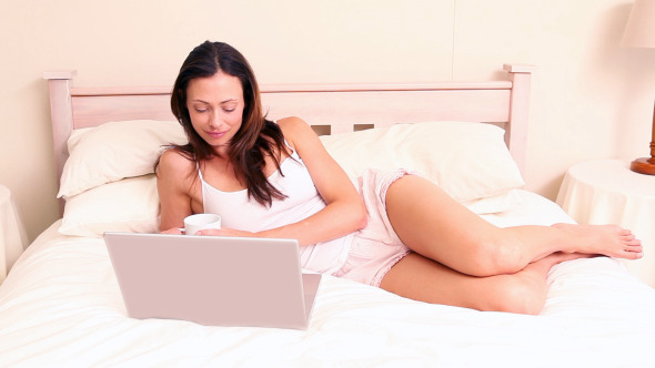 Smiling Brunette Lying On Bed Using Laptop
