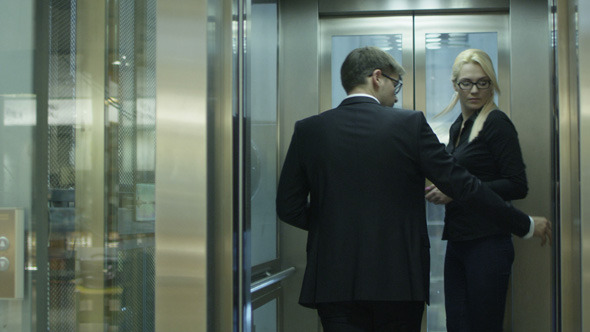 Businessman and Woman are Getting on the Elevator