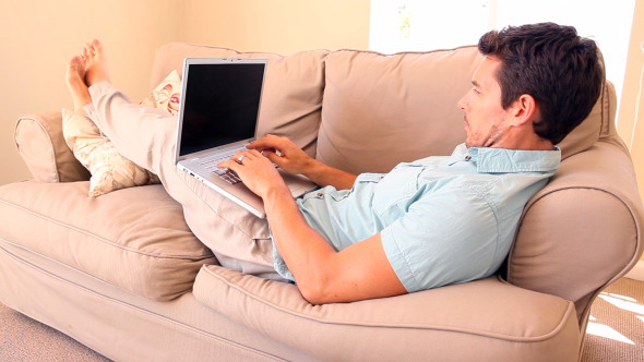 Man Lying On Couch Typing On Laptop