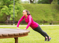 smiling woman doing push-ups on bench outdoors - PhotoDune Item for Sale