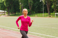 smiling woman running on track outdoors - PhotoDune Item for Sale